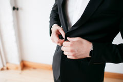 Making business look good. Close-up of man buttoning his jacket while standing against white background Royalty Free Stock Photo