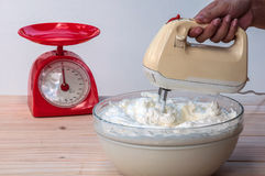 Making butter cream cake. Using hand mixer stock image