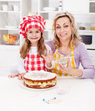 Making a cake for my birthday. Little girl with mother in kitchen Royalty Free Stock Images