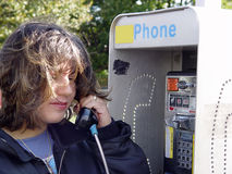 Making a Call. Photo of a Woman Using a Public Pay Pay Phone Royalty Free Stock Photo