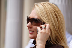 Making a call. Attractive lady taking a call on her mobile phone, wearing fashionable sunglasses royalty free stock image