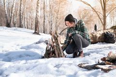 Making a campfire in a snowy birch forest royalty free stock photo