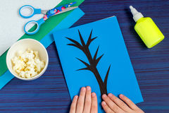 Making card by a child on spring theme. Step 4. Making card by a child on spring theme. Blossoming tree on a blue background. Original children`s art project royalty free stock photography