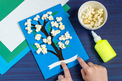 Making card by a child on spring theme. Step 6. Making card by a child on spring theme. Blossoming tree on a blue background. Original children`s art project Stock Photo