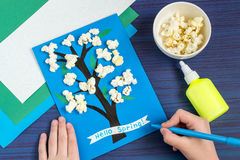 Making card by a child on spring theme. Step 7. Making card by a child on spring theme. Blossoming tree on a blue background. Original children`s art project stock images