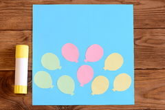 Making a card with paper air balloons. Step. Tutorial for kids. Card with paper air balloons, glue stick on a wooden table Stock Image