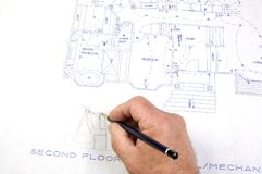 Making changes to Blueprints. Contractor making changes to a set of building plans for a custom house with draughting tools Stock Photography