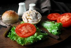 Making chicken sandwich with tomatoes, green salad, yogurt based sauce and mustard Stock Photo