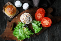 Making chicken sandwich with tomatoes, green salad, yogurt based sauce and mustard Stock Photos