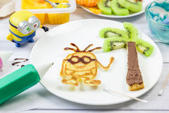 Making children breakfast with pancakes and fruits. Cartoon hero. Royalty Free Stock Photo