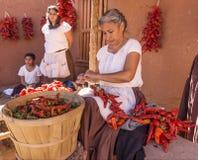 Making chili riestras. Woman stringing a chili riestra at Rancho Las Golondrinas near Santa Fe, New Mexico Royalty Free Stock Photography