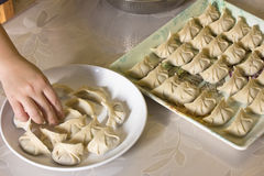 Making chinese dumplings. Chinese dumpling is one of the most important foods in Chinese New Year. Since the shape of Chinese dumplings is similar to ancient Stock Image