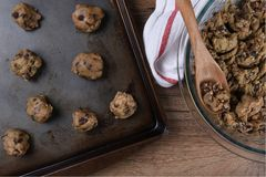 Making Chocolate Chip Cookies. Top view of a baking sheet with raw cookie dough for making Chocolate Chip Cookies, with a bowl of dough, spoon and towel Royalty Free Stock Photography