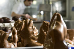 Making chocolate figurines in a bakery. Close-up of figurines, baker in background Royalty Free Stock Photos