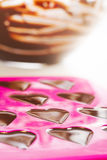 Making Chocolates. Warm chocolate just poured into chocolate mold Stock Image