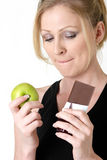 Making a choice. Attractive blond caucasian woman holding an apple and chocolate bar trying to decide which one to eat while biting on her lip royalty free stock photography