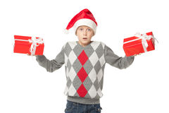 Making a choice. Confused boy in Santa hat holding two presents, over white background Royalty Free Stock Photography