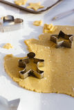 Making Christmas Biscuits with Gingerbread Man, Star and Heart Cookie Cutters on White Table. Vertical food scene of rolled out sweet cookie dough on white table Royalty Free Stock Images