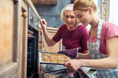 Happy grandmother and her teenage granddaughter removing Christmas cookies from stock image