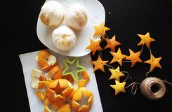 Making Christmas decorations from orange peels. Flat table view of stars made of orange t peels. Stars are cut from the peels and thread is led through them Royalty Free Stock Image