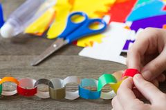 Making christmas paper chains by kid. Concept Stock Image