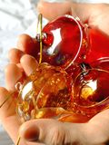 Making the Christmas tree. Red and golden Christmas glass ornaments in a man's hand Royalty Free Stock Photo