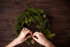 Making Christmas wreath with hands on wooden background. Making Christmas wreath with hands on brown wooden background Royalty Free Stock Photo