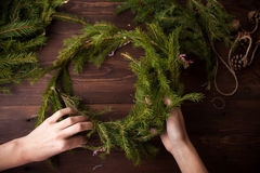 Making Christmas wreath with hands on wooden background. Making Christmas wreath with hands on brown wooden background Royalty Free Stock Image