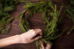 Making Christmas wreath with hands on wooden background. Making Christmas wreath with hands on brown wooden background royalty free stock photos