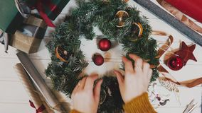 Making Christmas wreath in timelapse,top view pretty women hands making wreath in lamplight.  stock video