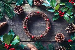 Making Christmas wreath using fresh and all natural materials. Christmas wreath with red berries and cones on wooden table royalty free stock images