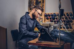 Making clothes. tailor sitting at table and working on a sewing machine at the sewing workshop. Making clothes. tailor sitting at table and working on a sewing Royalty Free Stock Image