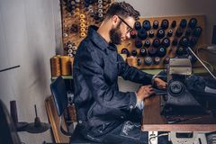 Making clothes. tailor sitting at table and working on a sewing machine at the sewing workshop. Making clothes. tailor sitting at table and working on a sewing Royalty Free Stock Photo