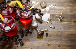 Making cocktail of berries , ice and lemon on wooden background. Royalty Free Stock Image