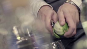 Making a Cocktail. Close-up shot of bartender`s hands cutting raw, ripe and fresh green lime on black cutting desk. Exotic fruity beverage preparation stock footage