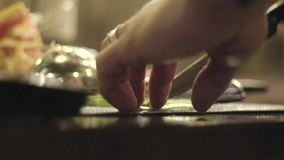 Making a Cocktail. Close-up shot of bartender`s hands cutting raw, ripe and fresh lemon on black cutting desk. Exotic fruity beverage preparation composition stock video footage