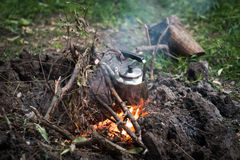 Making coffee on campfire. A pot of coffee boiling on a campfire Stock Photography
