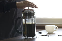 Making of coffee in French press. Man preparing coffee in French press coffee maker in warm morning light Royalty Free Stock Photography