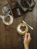 Making coffee on an old wooden table. Photo of a messy rustic wooden table of coffee beans, grinder and a woman`s hand holding a finished cup stock photography
