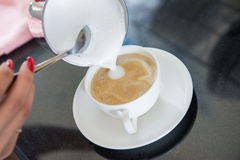 Making coffee: putting milk Royalty Free Stock Photo