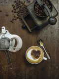 Making coffee on a rustic old wooden table. Photo of a messy rustic wooden table of coffee beans, grinder and a cup of coffee with heart-shaped chocolate royalty free stock image