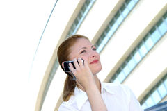Making connections.. Business woman making a telephone call using her cell phone outside an office building.  Horizontal orientation Royalty Free Stock Image
