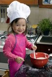 Making Cookies 008. Two young sisters have fun in the kitchen making a mess....I mean making cookies. Education, learning, cooking, childhood royalty free stock image