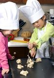 Making Cookies 014. Two young sisters have fun in the kitchen making a mess....I mean making cookies. Education, learning, cooking, childhood Royalty Free Stock Image