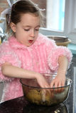 Making cookies. Young girl mixing food ingredients in a bowl with her hands Stock Photo