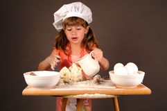 Making cookies. A cute young girl mixing her ingredients to make cookie dough and wearing a chefs hat and apron royalty free stock image
