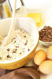 Making Cookies. Making chocolate chip cookies. Mixing bowl, wooden spoon, butter, choc chips and eggs stock images
