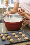 Making cookies. Close up of Hispanic mother and child in kitchen making cookies royalty free stock image