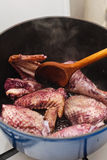 Making coq au vin. Cooking parts of a rooster for coq au vin in a cast iron pot Stock Photos