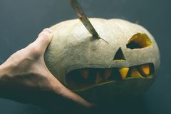 Making a pumpkin jack o lantern with carved teeth for halloween concept d royalty free stock photo